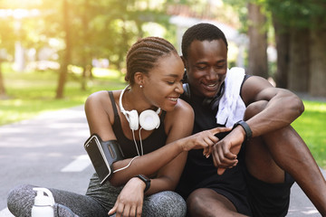 Black Couple Using Smartwatch Fitness Tracker After Outdoor Workout, Checking Burned Calories