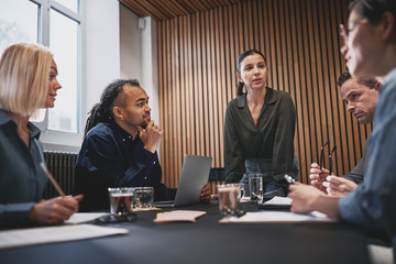 Young businesswoman talking with colleagues during a boardroom m