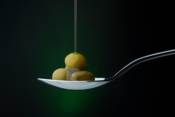 green olives on a spoon on a dark background, stream of olive oil