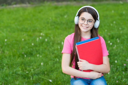 Girl listening summer melody wireless headphones nature background, back to school concept