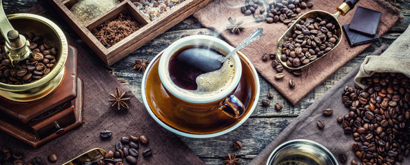 A cup of aromatic black coffee, a coffee grinder, a coffee maker, coffee beans of different varieties on the table. Morning espresso or Americano coffee for breakfast in a beautiful brown cup.