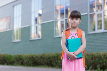 Cute little schoolgirl with backpack holding notebooks on the yard