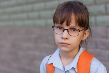 Portrait of sad schoolgirl with glasses and backpack isolated on a brick green wall