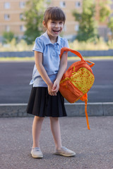 Portrait of happy schoolgirl with backpack isolated on a school yard