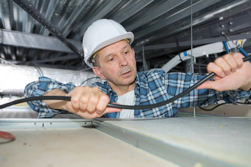 man fixing wires on the ceiling