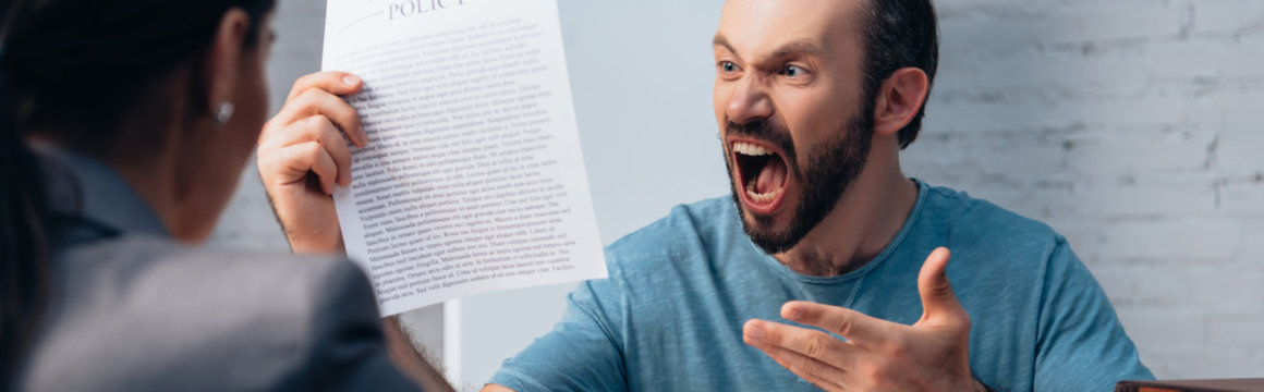 panoramic shot of angry and bearded man screaming while holding insurance policy agreement near lawyer