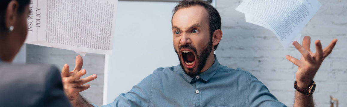 panoramic concept of angry and bearded man screaming while throwing in air documents near lawyer