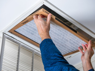 Man replacing dirty HVAC air filter in ceiling vent. Home air duct system maintenance for clean air.