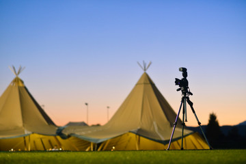 Tent with teepees at night with tripod and camera.