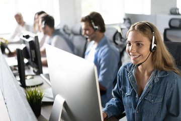 Obraz How can I help you? Beautiful call center workers in headphones are working at modern office. - fototapety do salonu