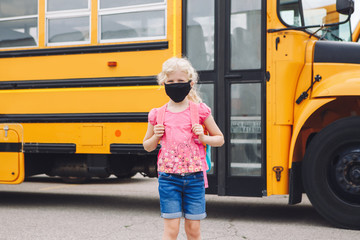 Happy Caucasian girl student wearing face mask near yellow bus. Kid with personal protective equipment on face. Education and back to school in September. A new normal during coronavirus.