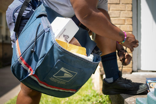 United States Postal Service (USPS) employee stops to tie shoe laces while delivering mail in Houston, Texas