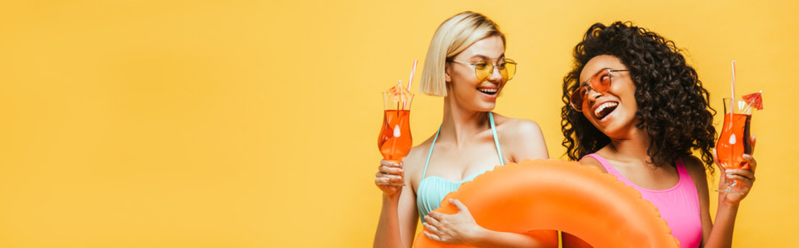 young interracial women in summer outfit holding swim ring and cocktail glasses while looking at each other isolated on yellow