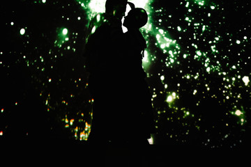 Couple dancing together in dark room with projection of starry sky