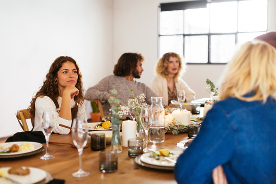 Woman listening to story during family dinner