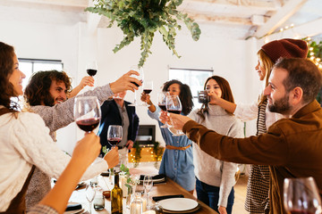 Happy family clinking wineglasses over table