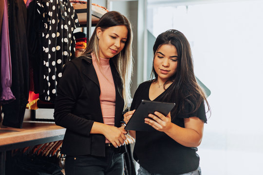 Latin woman owner of small business. Entrepreneurial woman working in her clothing store.