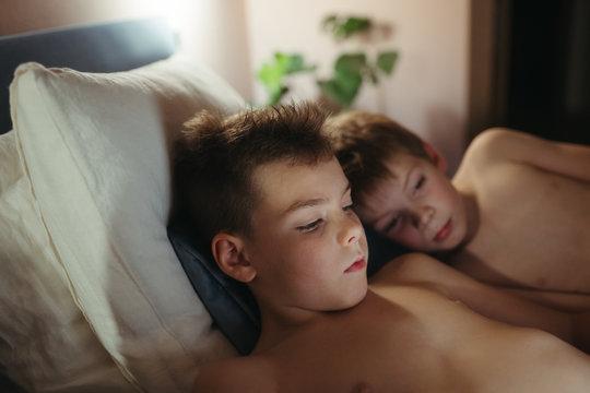 Kids enjoying reading ebook in cozy bedroom.