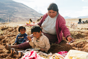 Indigenous siblings having lunch together in the mountains of peru