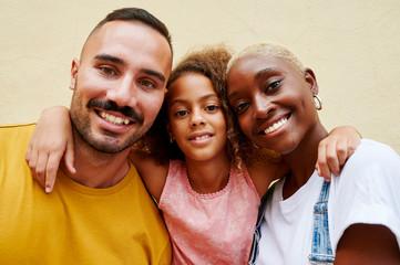 Smiling family standing outside