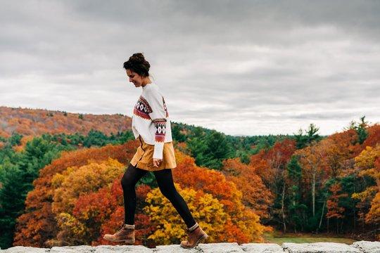 teen girl walking a wall in the fall