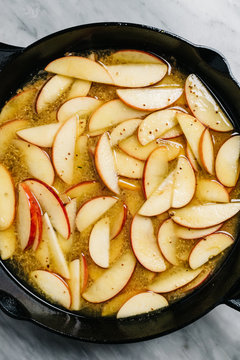 Cooking down apples in cider in an iron skillet