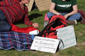 Sitzende Teilnehmer mit Plakaten an einer Corona-Demonstration gegen Maskenpflicht in Deutschland
