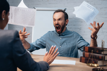 selective focus of angry and bearded man screaming while throwing in air documents near lawyer