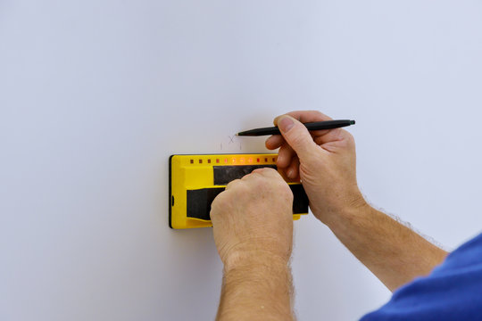Uses Multi-Sense Technology to find studs more accurately through difficult surfaces. Man hand is scanning wall by