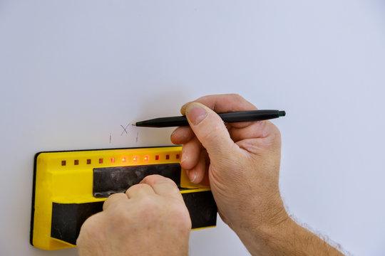 Digital detector man hand is scanning wall by sensors ProSensor precision stud finder wooden beams