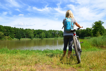 Woman with bicycle standing on shore of lake. Outdoor recreation.