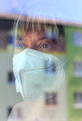 Woman in a protective medical mask looking out of the window. Quarantine during the COVID-19 pandemic. Stay at home concept.