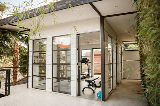 Private gym at home. Small gym in Luxury villa, big window, tropical view with palm trees skyline