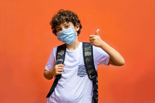 Schoolchild wearing a covid-19 surgical mask thumbs up. Back to school at new normal after coronavirus quarantene lockdown concept.