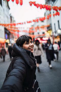 Chica joven y guapa sonriendo en chinatown