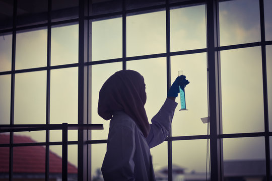 silhouette of a muslim woman scientist in laboratory