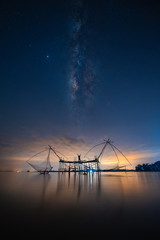 Wall Mural - Landscape image of milky way over traditional square fishnet equipment at Pakpra Canal, Phatthalung, Thailand