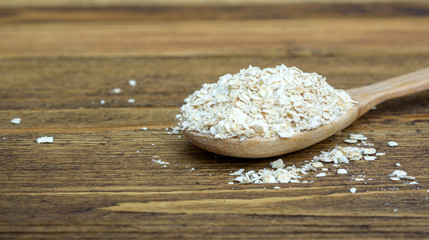 Oatmeal in a spoon on a wooden table.