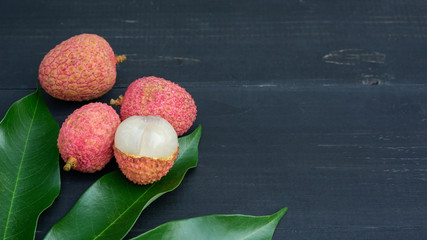 Red lychee on a black wooden table.
