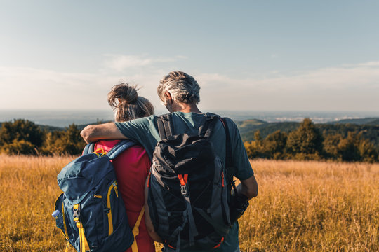 Active senior couple hiking in nature with backpacks, enjoying their adventure at sunset.