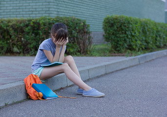tired schoolgirl with a headache sits on the ground. The girl holds on to her head