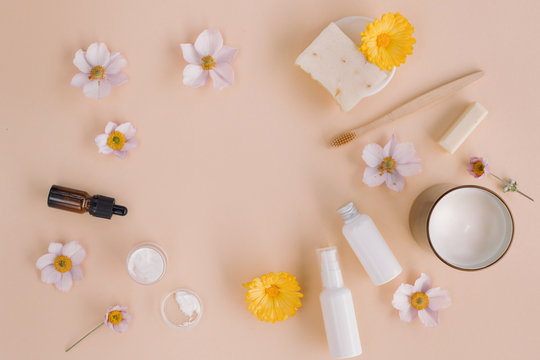Flat lay of beauty product mock ups, organic soaps, flower buds, candle on beige background. Skin care and body care concept.
