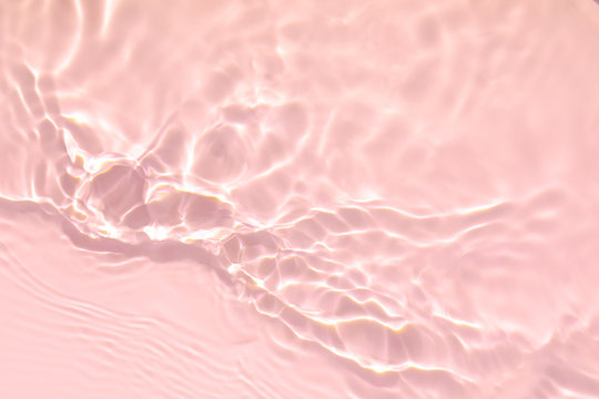 Closeup of pink transparent clear calm water surface texture with splashes and bubbles. Trendy abstract summer nature background. Coral colored waves in sunlight.