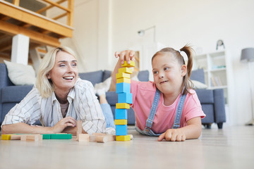 Little girl with down syndrome building a tower from colored blocks together with her mother on the floor at home