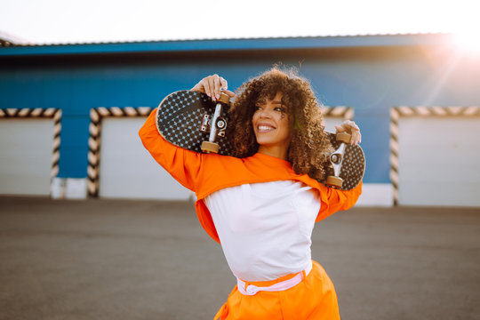 Stylish woman with curly hair in an orange suit posing with a skateboard. African American woman stands on the street with skateboard in hands. Lifestyle, youth concept.