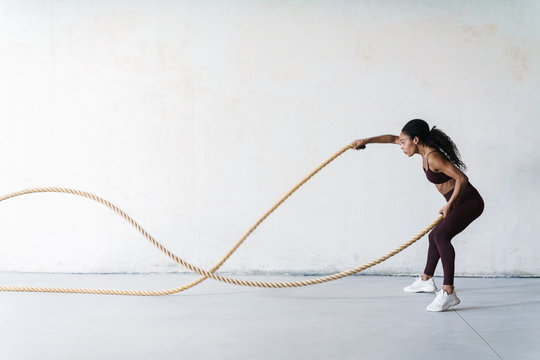 Portrait of young african american woman doing workout with battle rope
