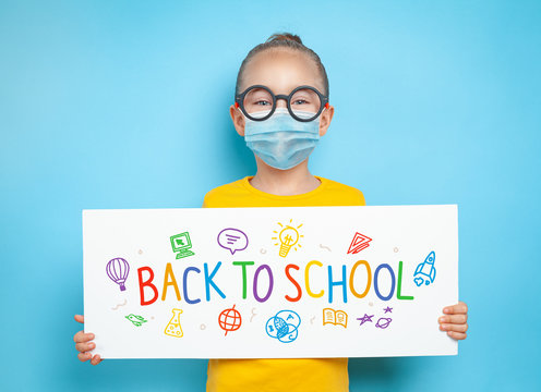Beautiful cute little girl with glasses wearing protective medical mask and holding a white paper with message