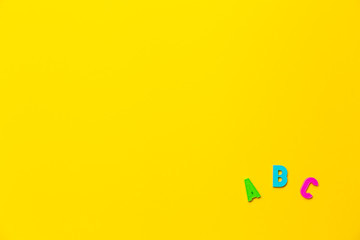 Multicolored letters A, B, C of the alphabet on yellow background. Learning foreign language for...