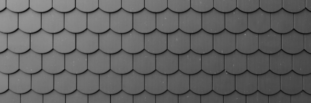 Fragment of a black roof of a private house made of shingles