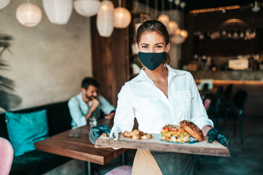 Beautiful young waitress with face protective mask serving delicious burger to middle age male customer. Corona virus and small business is open for work concept.